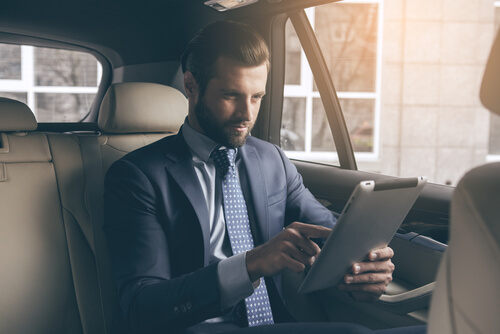 man checking email in car