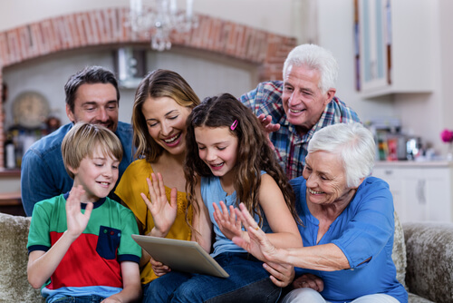 large family keeping in touch with relative over video chat