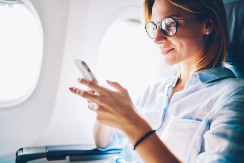 business woman using travel apps on phone