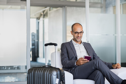 Business Man looking at phone in airport
